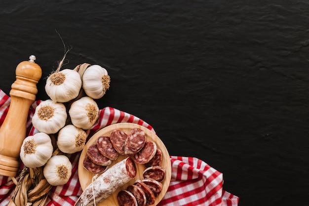 Alho e salsichas perto de especiarias no guardanapo