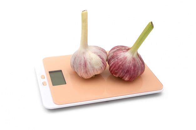 Alho em balanças de cozinha em branco. o conceito de pesagem.