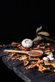 Alho, frutos secos e sementes na superfície rústica escura. foto artística de alho e frutas secas na mesa preta velha, filmado em estilo ciaroscurro baixa chave