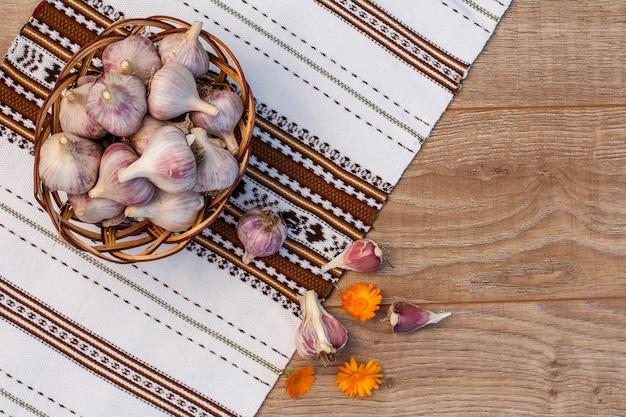Alho maduro em uma cesta de vime deitado na toalha com ornamento étnico ucraniano na placa de madeira. apenas vegetais colhidos. vista do topo