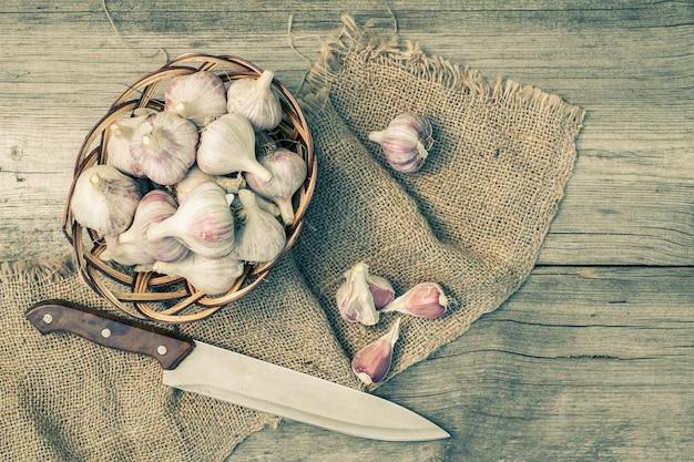 Alho maduro em uma cesta de vime e uma faca de aço inoxidável deitado sobre um pedaço de pano de saco e tábua de madeira. apenas vegetais colhidos.