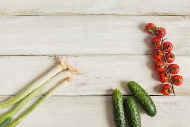 Alho-poró orgânico verde cru; pepino e tomate cereja na mesa de madeira