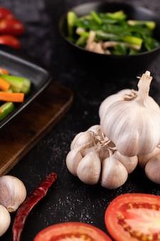 Alho, tomate e garfos para cozinhar. foco seletivo.