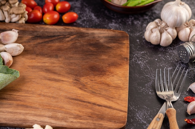 Alho, tomate, tábua de cortar e garfo de cozinha.