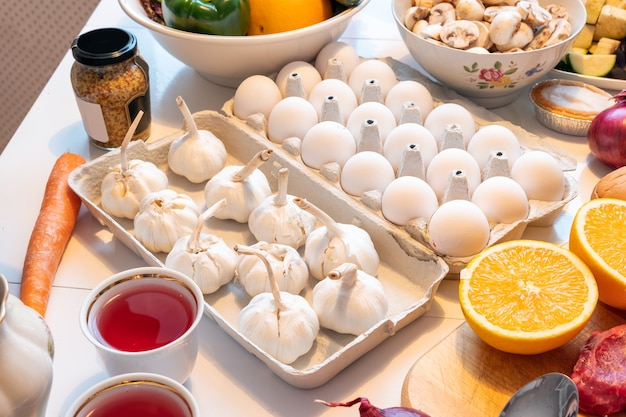 Alhos com ovos na bandeja com frutas e carnes se preparando para cozinhar na mesa de madeira