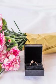 Aliança de casamento com buquê de flores na mesa