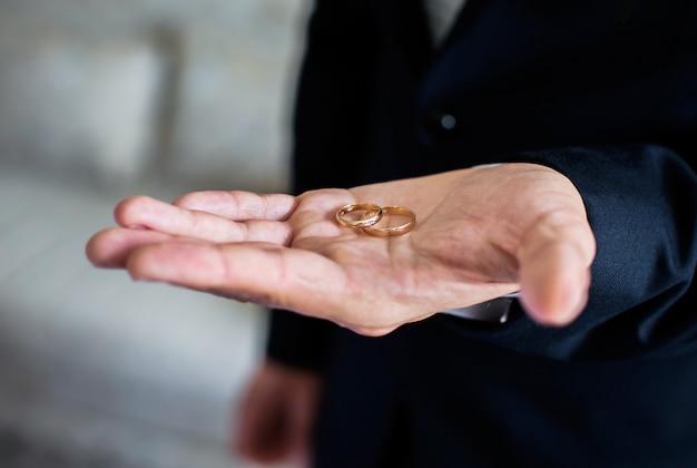 Aliança de ouro na mão de um homem, o noivo segurando anéis, faixas de casamento