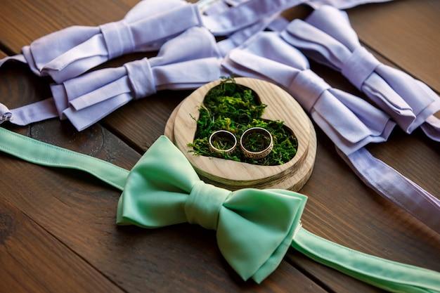 Aliança em caixa de anel em forma de coração com musgo verde perto de laços para noivo e padrinhos