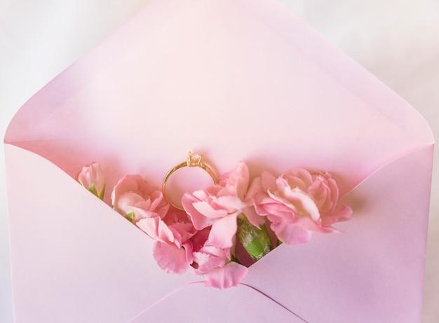 Aliança no envelope com flores cor de rosa
