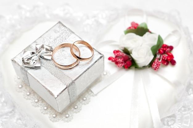 Alianças, caixa de presente e flores para a noiva.
