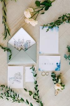 Alianças de casamento caídas no chão de ladrilhos cercadas por pinturas em aquarela, ramos verdes e flores
