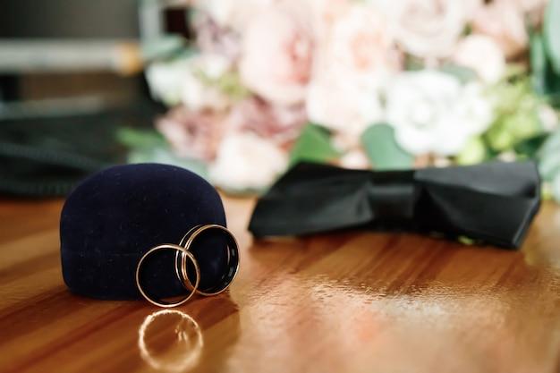 Alianças de casamento com a borboleta do noivo no assoalho de madeira.