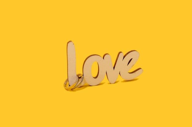 Alianças de casamento com a palavra de madeira amor em fundo amarelo. conceito dos namorados.