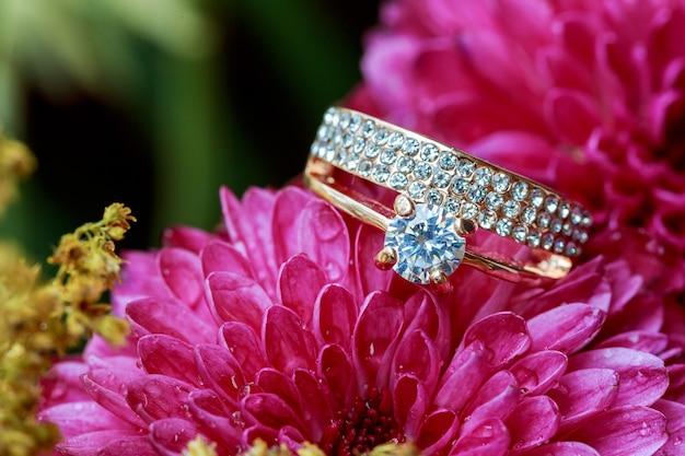 Alianças de casamento com diamantes em tons de rosa e suavizado, anéis, dálias cor-de-rosa amam o dia dos namorados