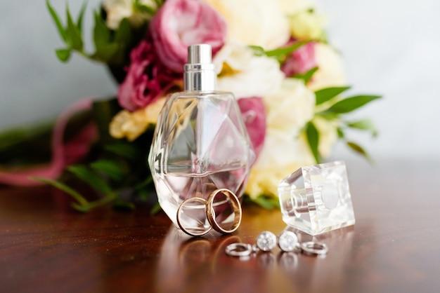 Alianças de casamento com perfume e um buquê de casamento na mesa de cabeceira. símbolos de casamento, atributos.