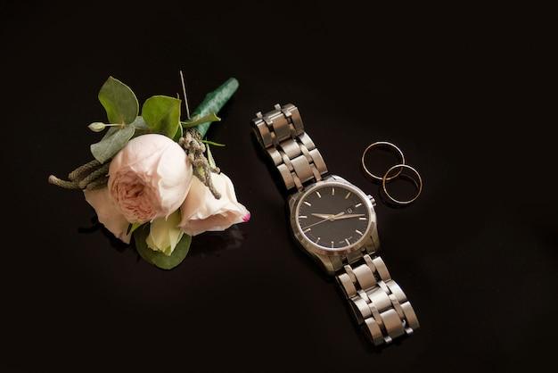 Alianças de casamento com relógio e rosas