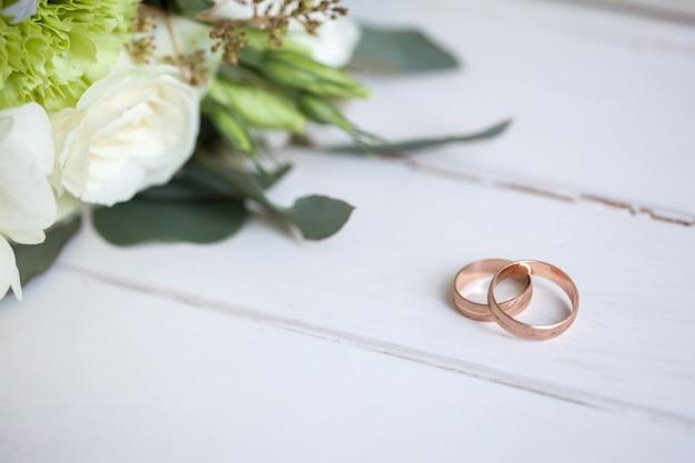 Alianças de casamento com rosas brancas na mesa de madeira