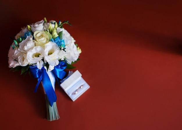 Alianças de casamento com um bouquet de noiva de rosas brancas