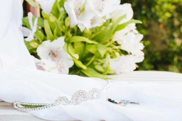 Alianças de casamento; coroa; lenço perto do buquê de flores na mesa