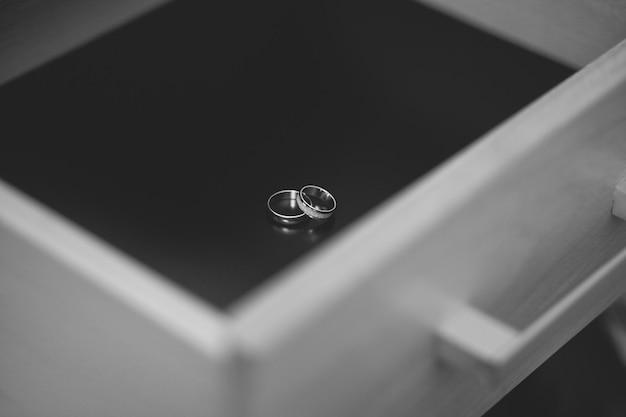 Alianças de casamento da noiva e do noivo em uma cômoda de madeira ou mesa de cabeceira.