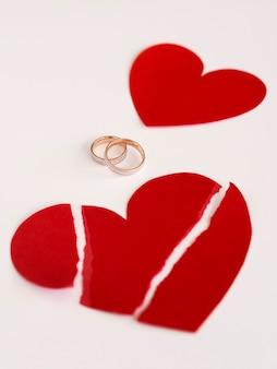 Alianças de casamento de alto ângulo e coração de papel quebrado
