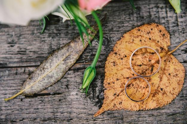 Alianças de casamento de ouro e fundo de textura de madeira