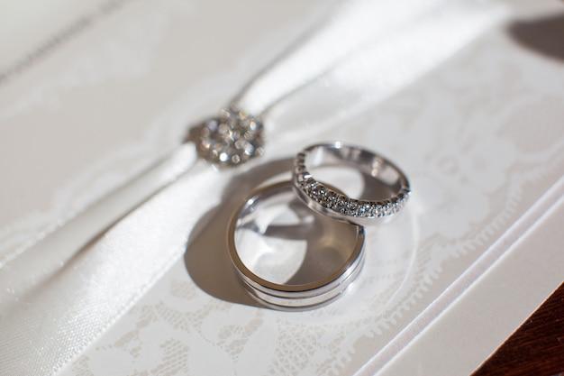 Alianças de casamento de prata elegantes feitas de ouro branco repousam na pulseira de cristal