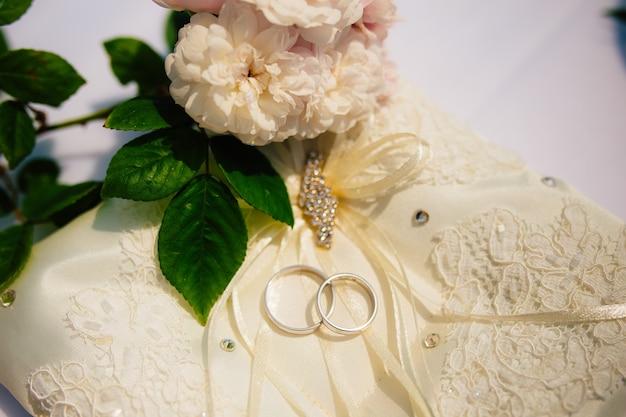 Alianças de casamento de um casal recém-casado em uma almofada para alianças