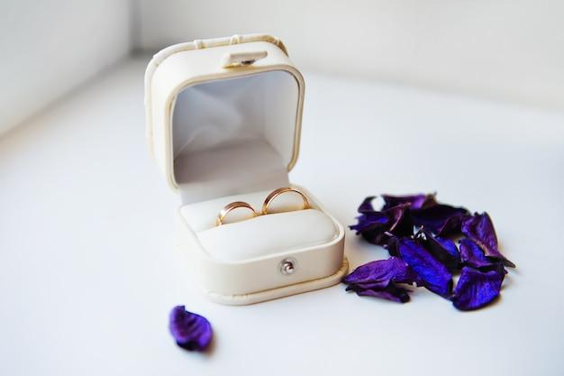 Alianças de casamento do noivo e a noiva em uma caixa branca