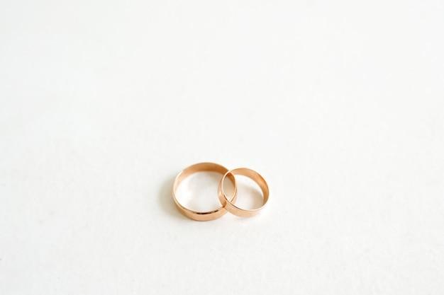 Alianças de casamento douradas isoladas no branco com espaço de cópia