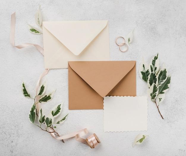 Alianças de casamento e cartões de convite com flores