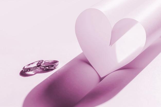 Alianças de casamento e coração em um branco