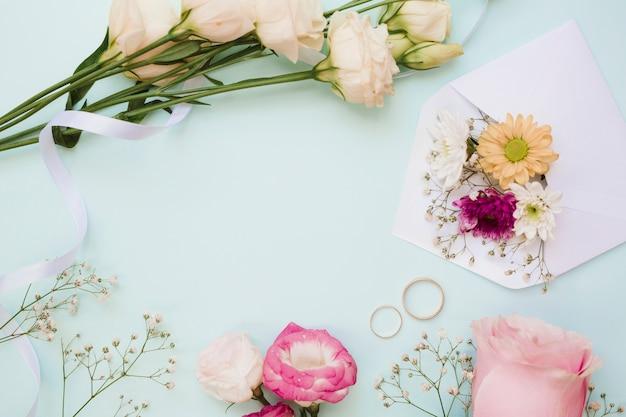 Alianças de casamento e decoração de flores sobre fundo azul pastel