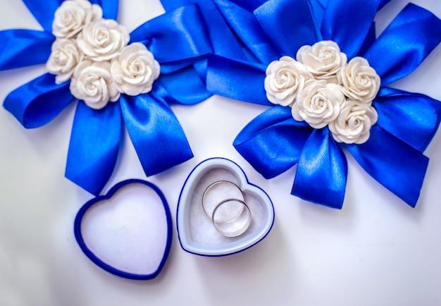 Alianças de casamento e flores de fitas azuis