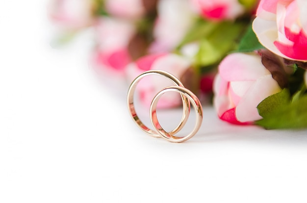Alianças de casamento e flores isoladas em branco