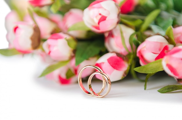 Alianças de casamento e flores isoladas no fundo branco