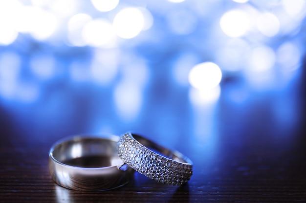 Alianças de casamento e luzes desfocadas na madeira