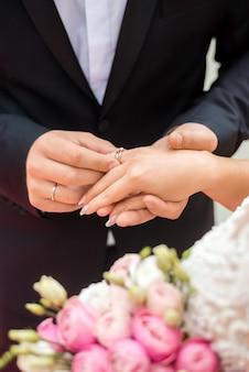 Alianças de casamento e mãos da noiva e do noivo. jovem casal de noivos na cerimônia. matrimônio. homem e mulher apaixonados. duas pessoas felizes celebrando se tornando família