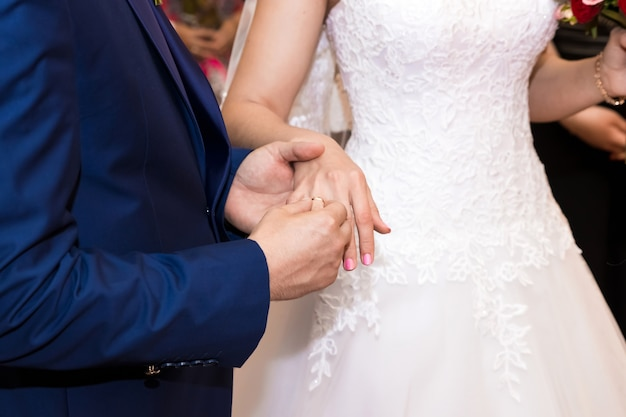 Alianças de casamento e mãos da noiva e do noivo. jovem casal de noivos na cerimônia.