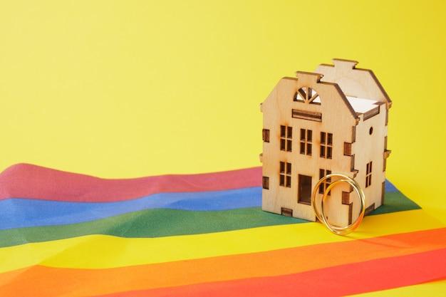 Alianças de casamento e modelo de casa de madeira e bandeira lgbtq
