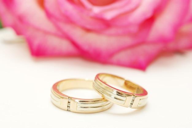 Alianças de casamento e rosa em branco