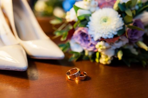 Alianças de casamento e sapatos para a noiva.