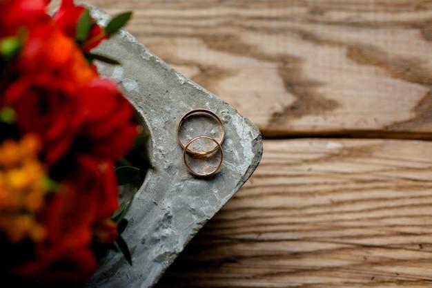 Alianças de casamento e um buquê de flores vermelhas em um fundo de madeira