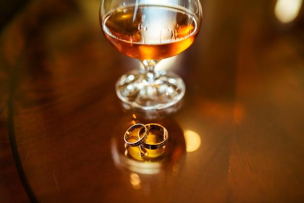 Alianças de casamento e um copo de conhaque.
