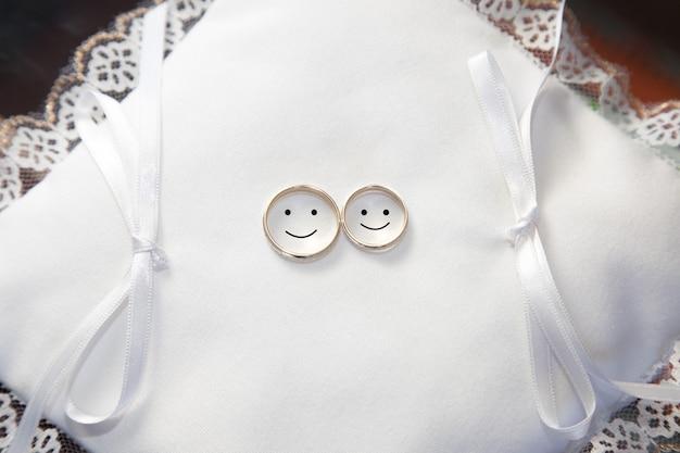 Alianças de casamento em bloco branco com rostos desenhados