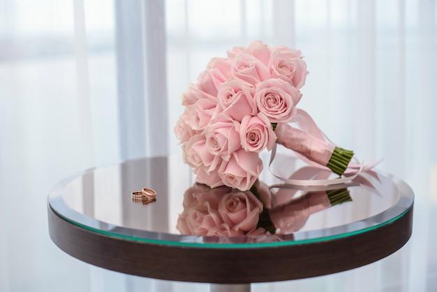 Alianças de casamento em cima da mesa com um buquê