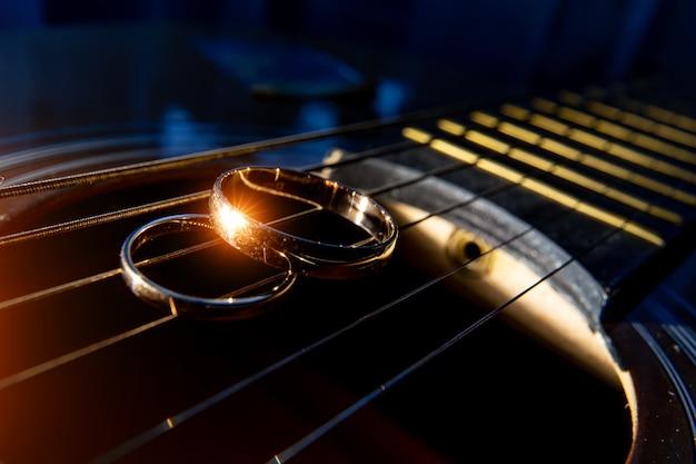 Alianças de casamento em close-up de cordas de guitarra em um fundo escuro.