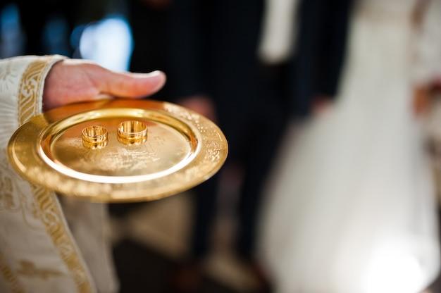 Alianças de casamento em disco na mão do padre