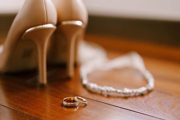 Alianças de casamento em textura de madeira com sapatos femininos de casamento e joias de noiva