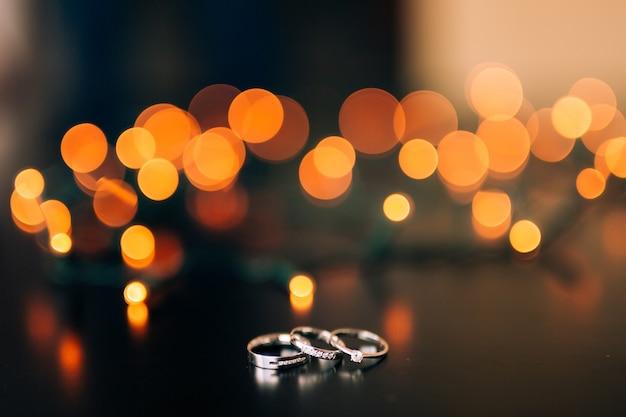 Alianças de casamento em um bokeh de fundo amarelo de guirlandas mágicas